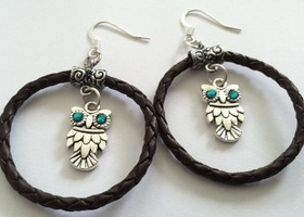 Large braided leather hoop earrings with silver tone owl charms and Swarovski crystal eyes.