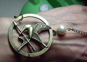 The Hunger Games pendant Mockingjay Arrow and Peeta pearl bracelet