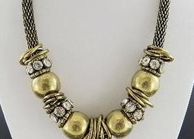 Chunky, gold tone and crystal loose beads float on a mesh necklace chain 20""